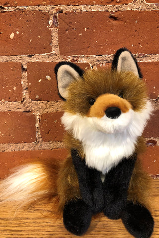 A stuffed animal red fox toy in front of a brick background.