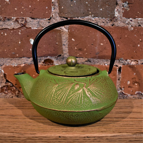 Green cast iron teapot with a gold design and a black handle.