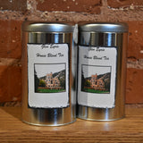 Two silver tea tins with an image of the Glen Eyrie Castle on the label.