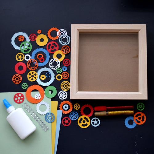 Craft kit containing wooden box Frame - 15cm x 15cm, assorted paper cogs in various colours, coloured paper, PVA glue and glitter glue tubes