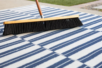Broom sweeping outdoor rug