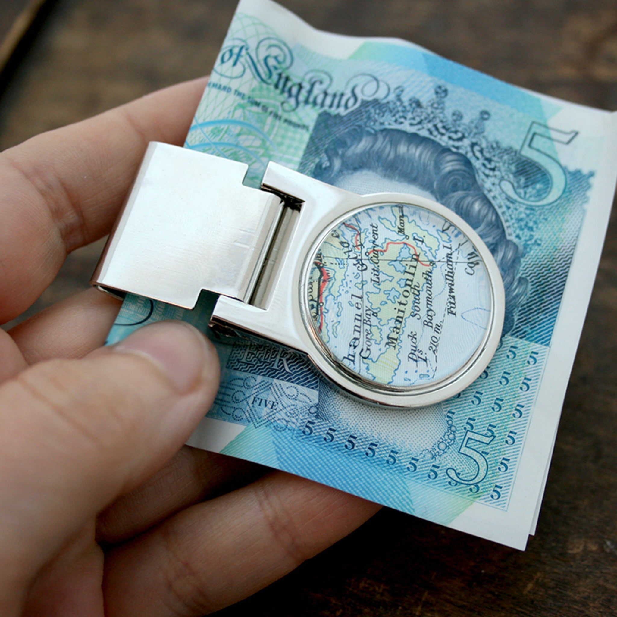 Hand holding money clip personalised with geographical map
