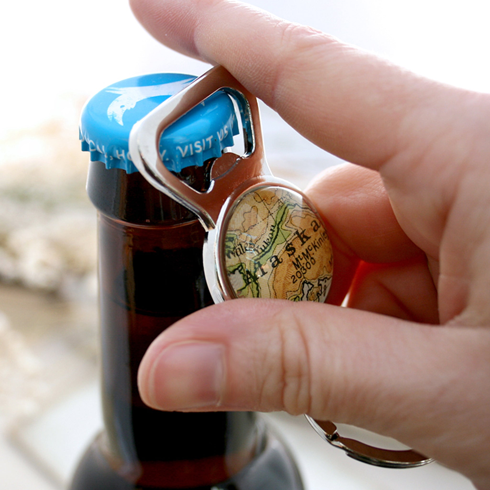 Opening a beer using Personalised Bottle Opener with map of Alaska featured