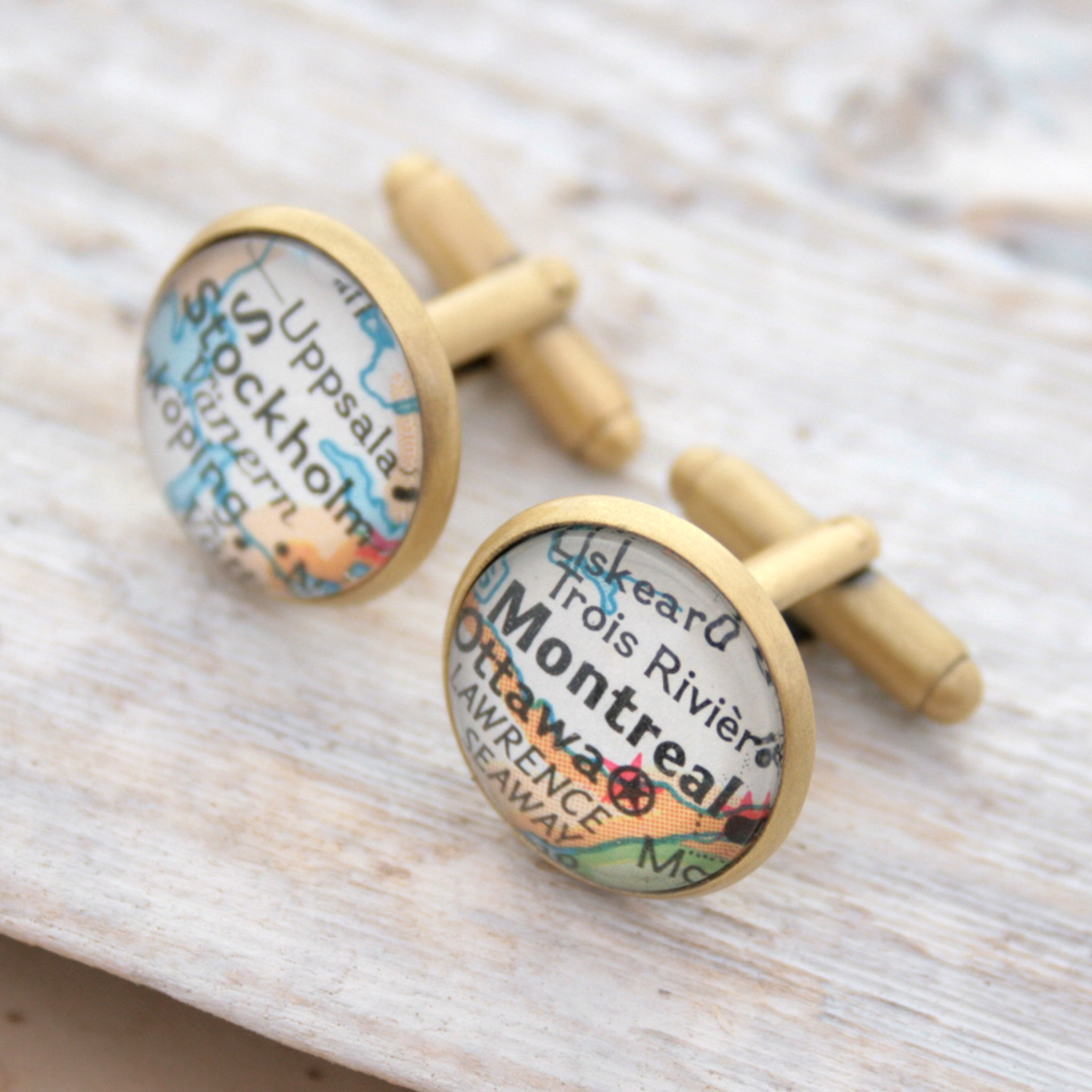 Personalised map cufflinks in brushed bronze color featuring maps of Stockholm and Montreal