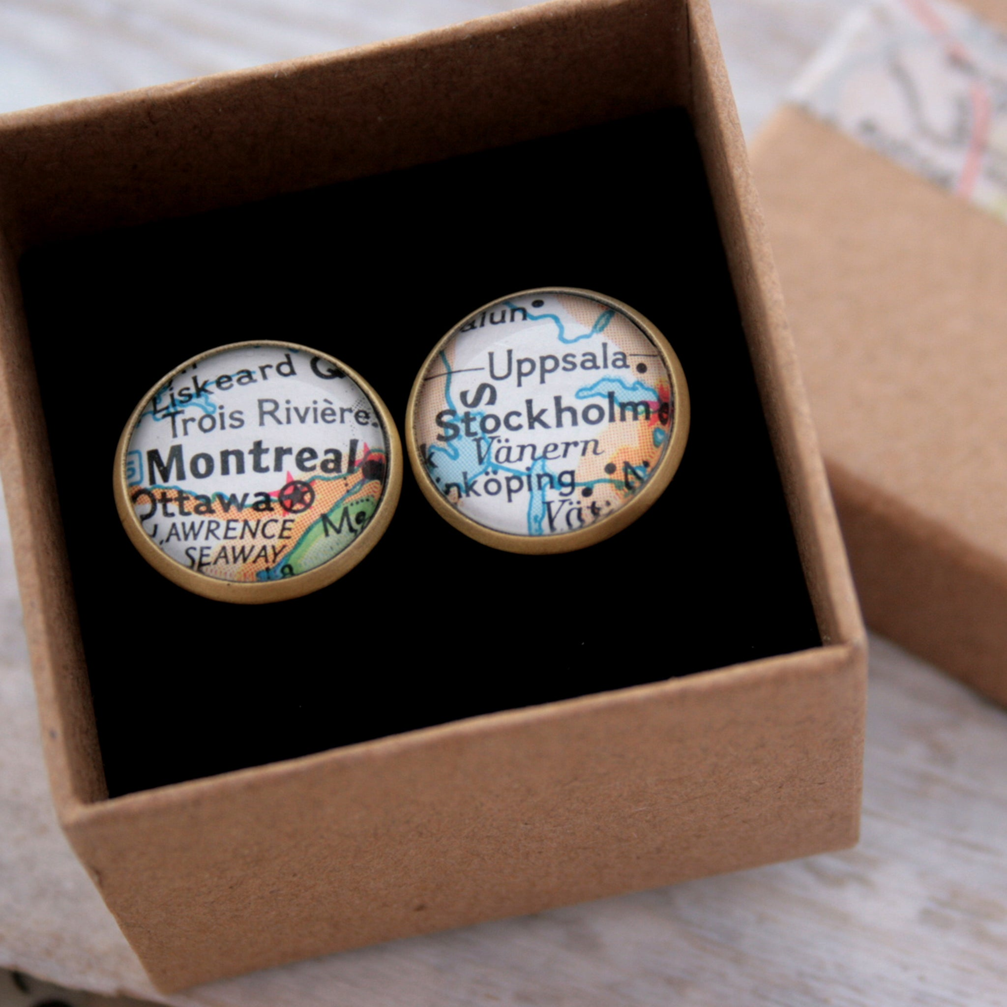 Personalised map cufflinks in antique bronze color featuring maps of Montreal and Stockholm in a box