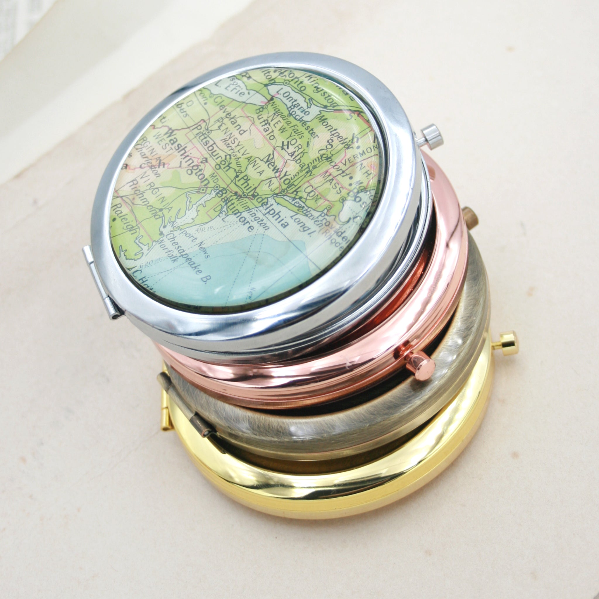 Four compact mirrors one on the another, gold, bronze,rose gold and silver featuring map of New York