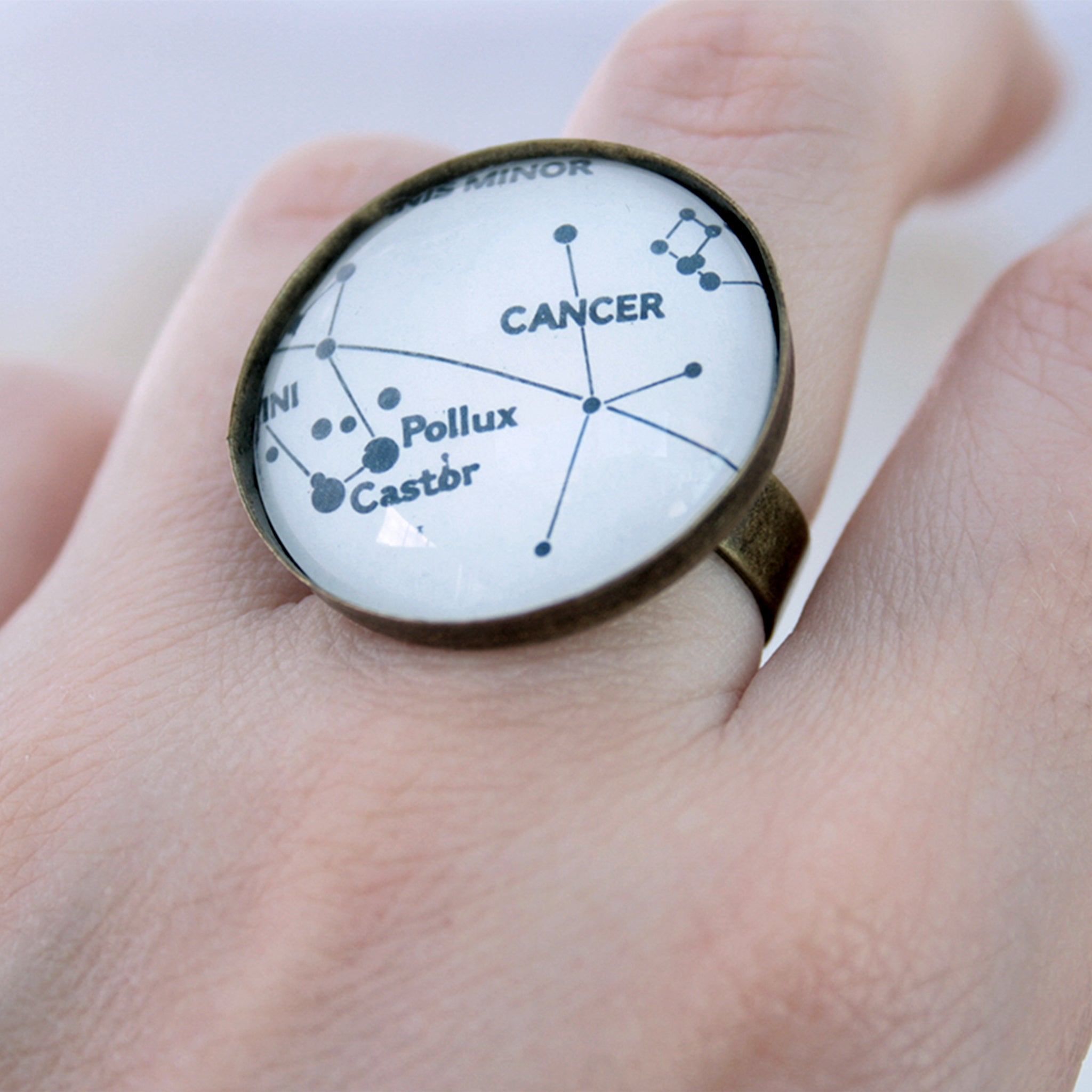 Large round bronze celestial ring worn on womans hand