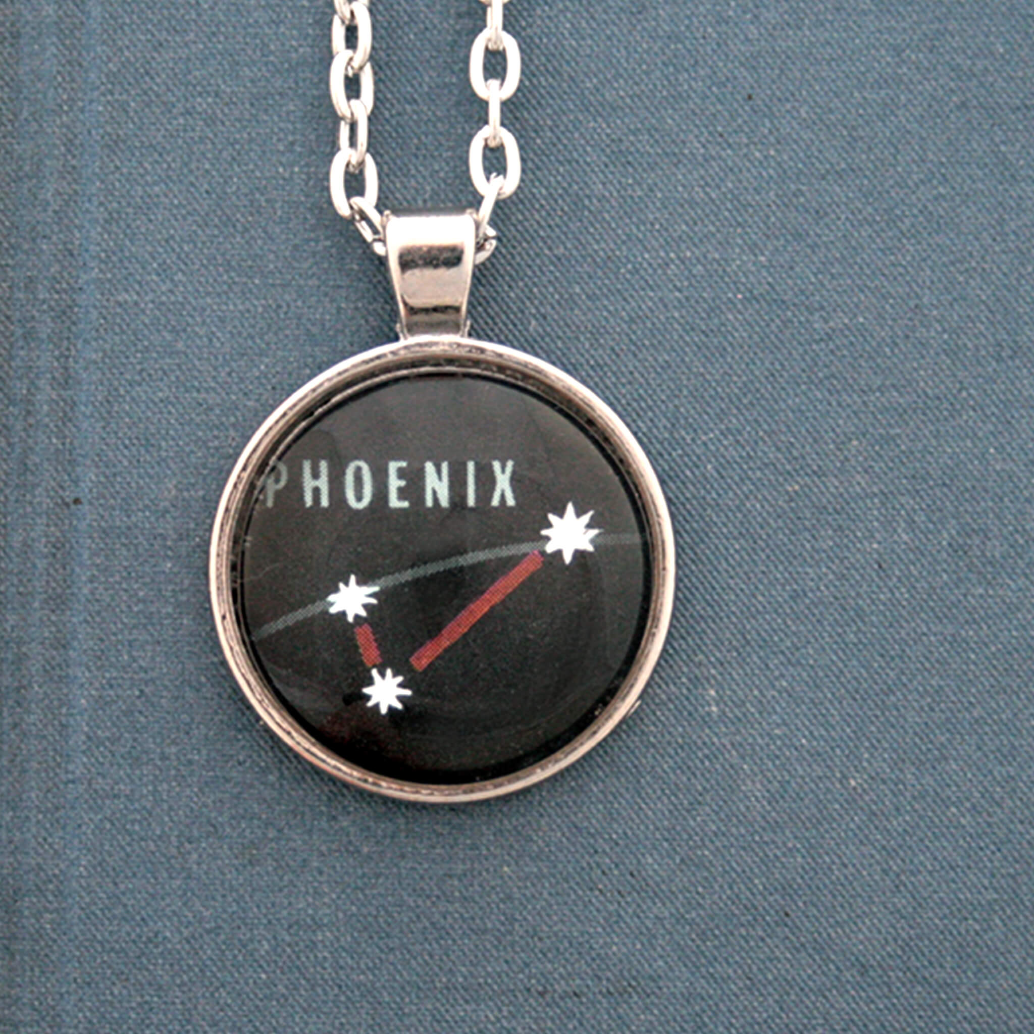 Silver tone pendant necklace with Phoenix constellation