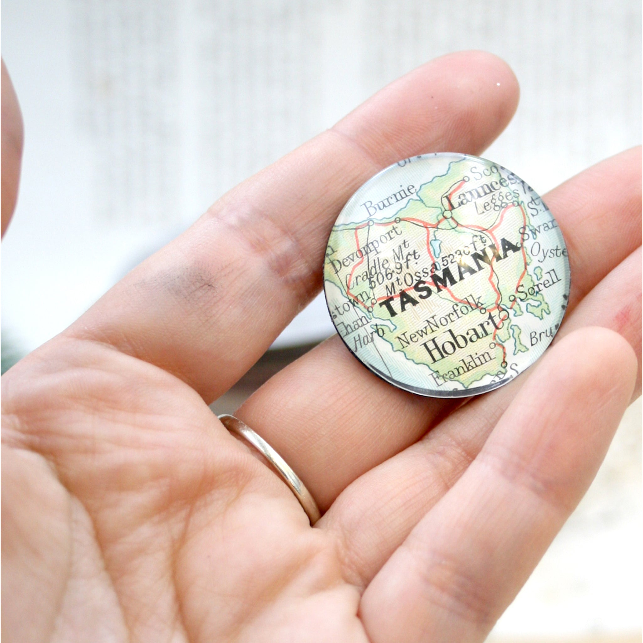 Hand holding a fridge magnet personalised with geographical map of custom locations