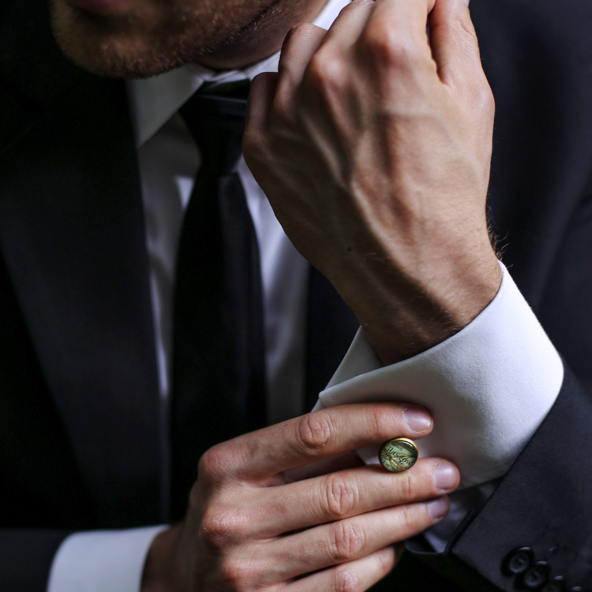 Man in a suit putting on pair of map cufflinks
