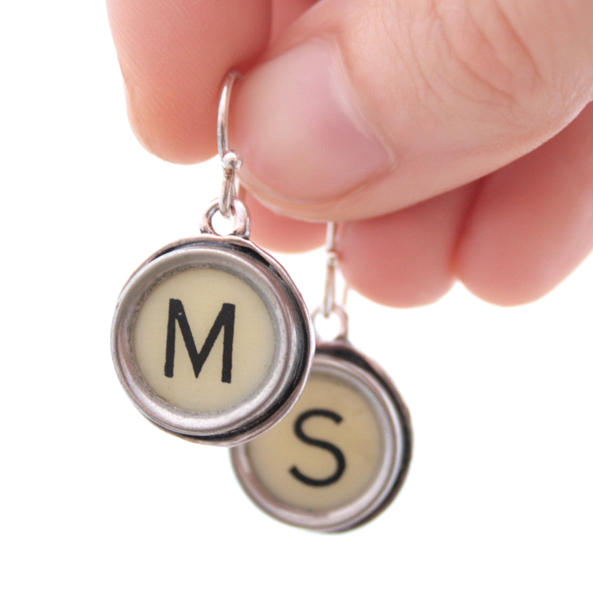 M and S Ivory Typewriter keys turned into initial earrings hold in hand