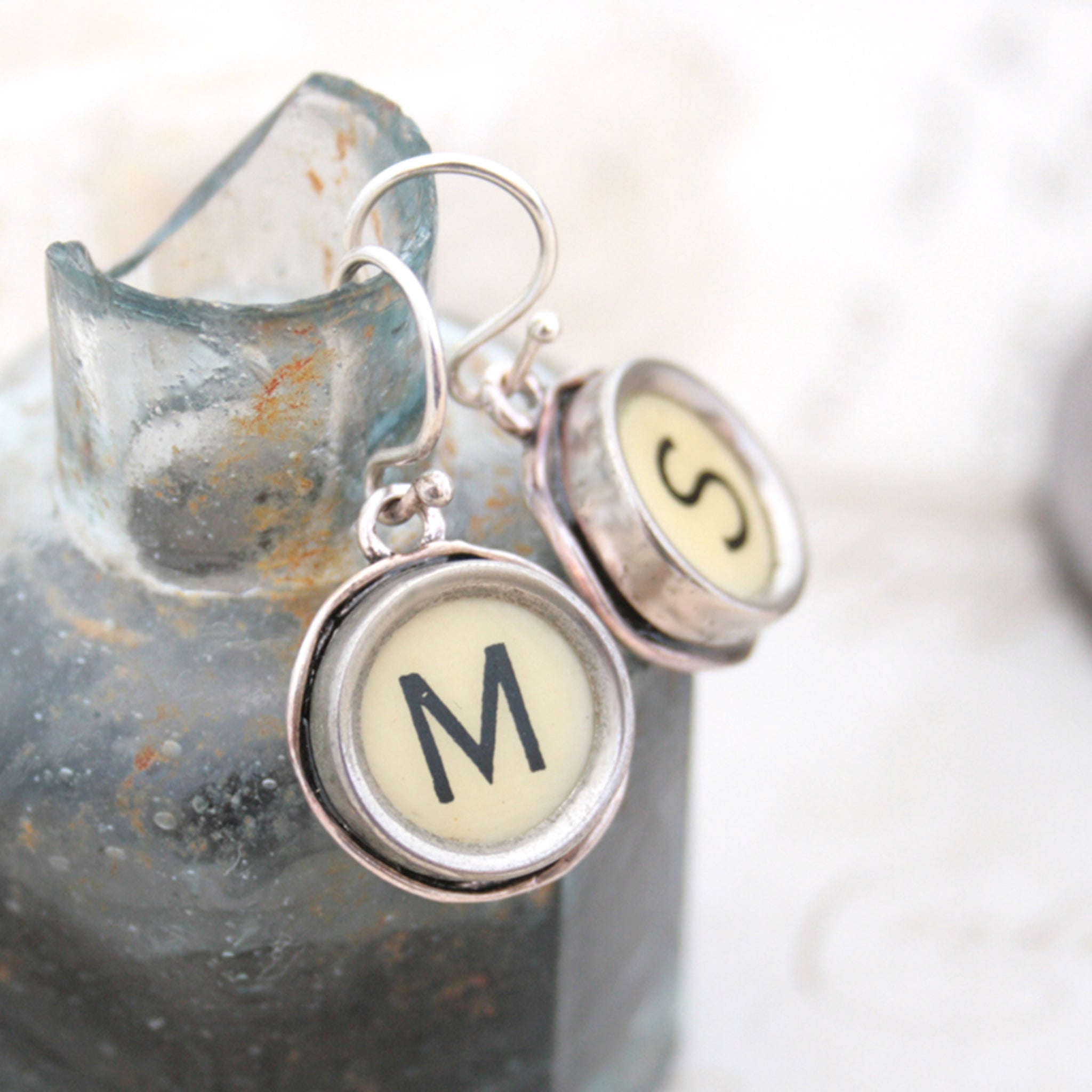 M and S Ivory Typewriter keys turned into initial earrings hanging on the edge of inkwell