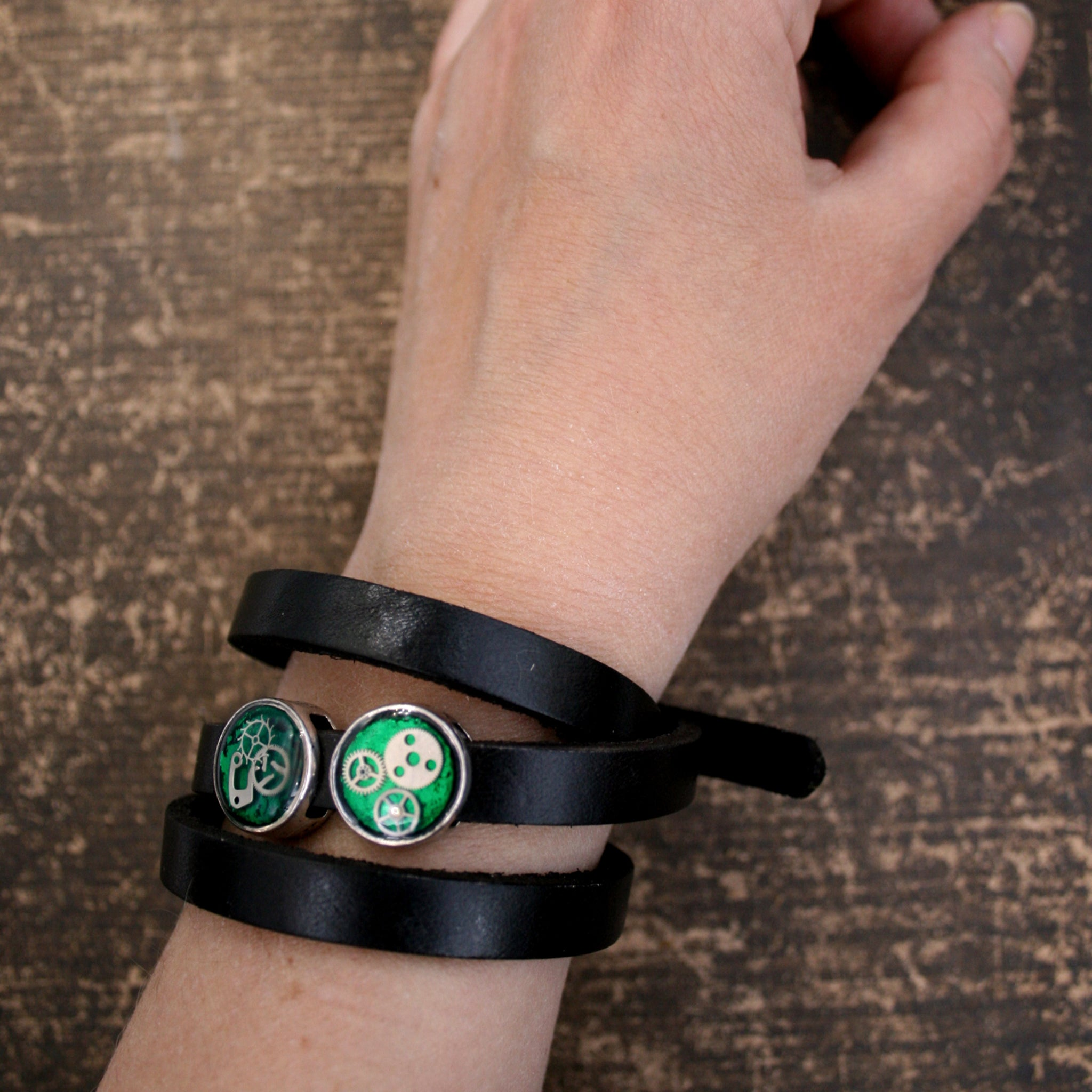 Black leather triple wrap bracelet with green steampunk slider beads with watch parts on hand