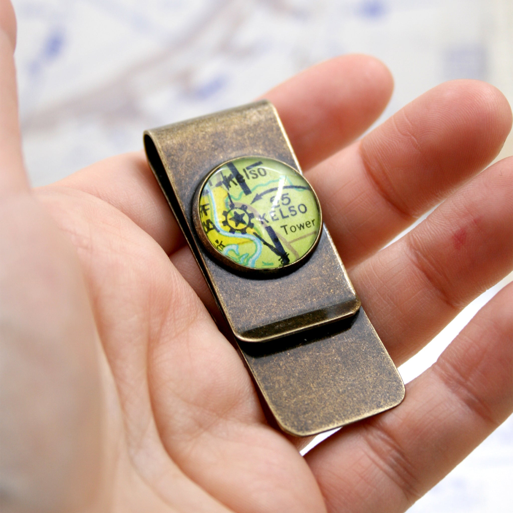 Hand holding Bronze money clip featuring aeronautical chart