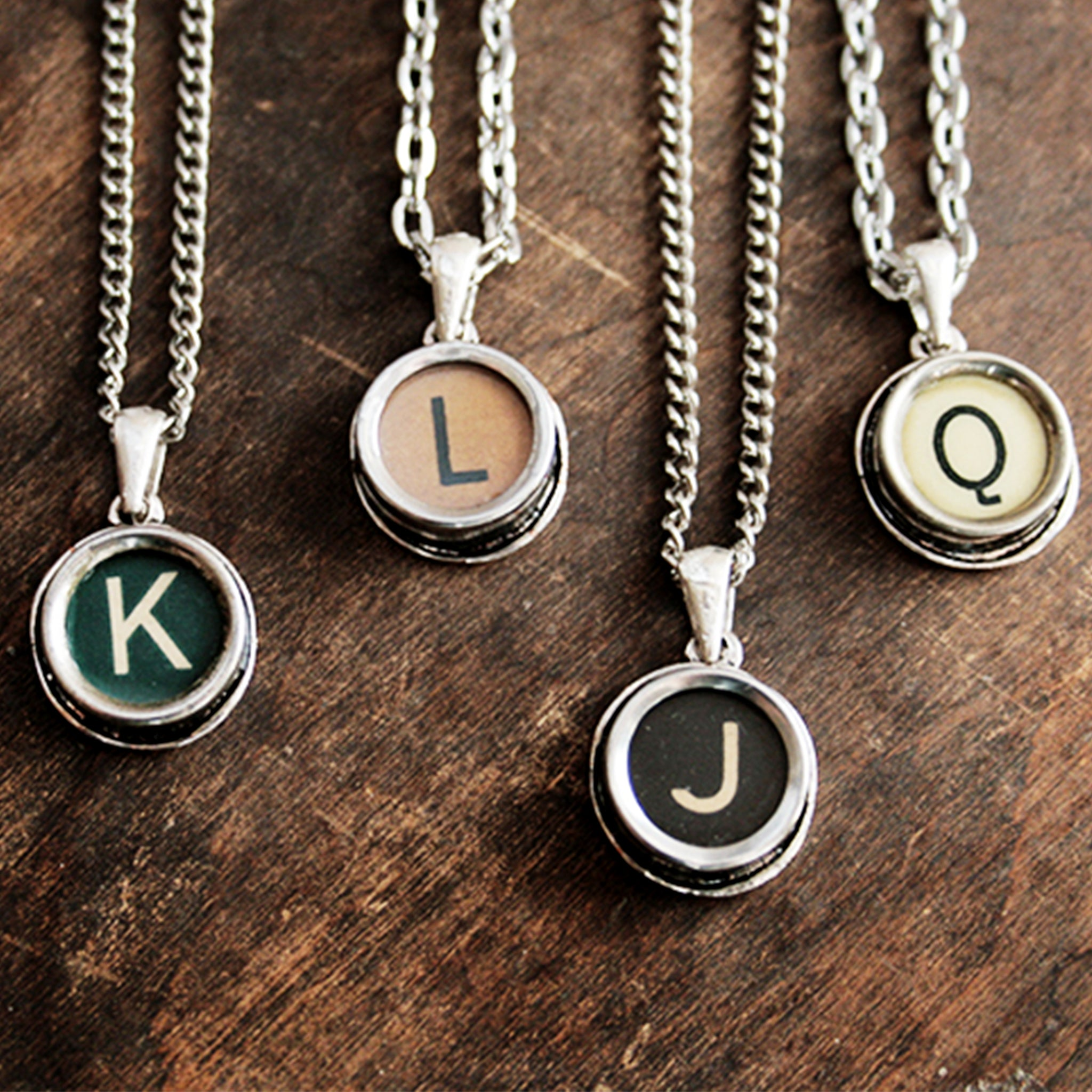 Four typewriter necklaces made of real typewriter keys in green, brown, black and ivory color