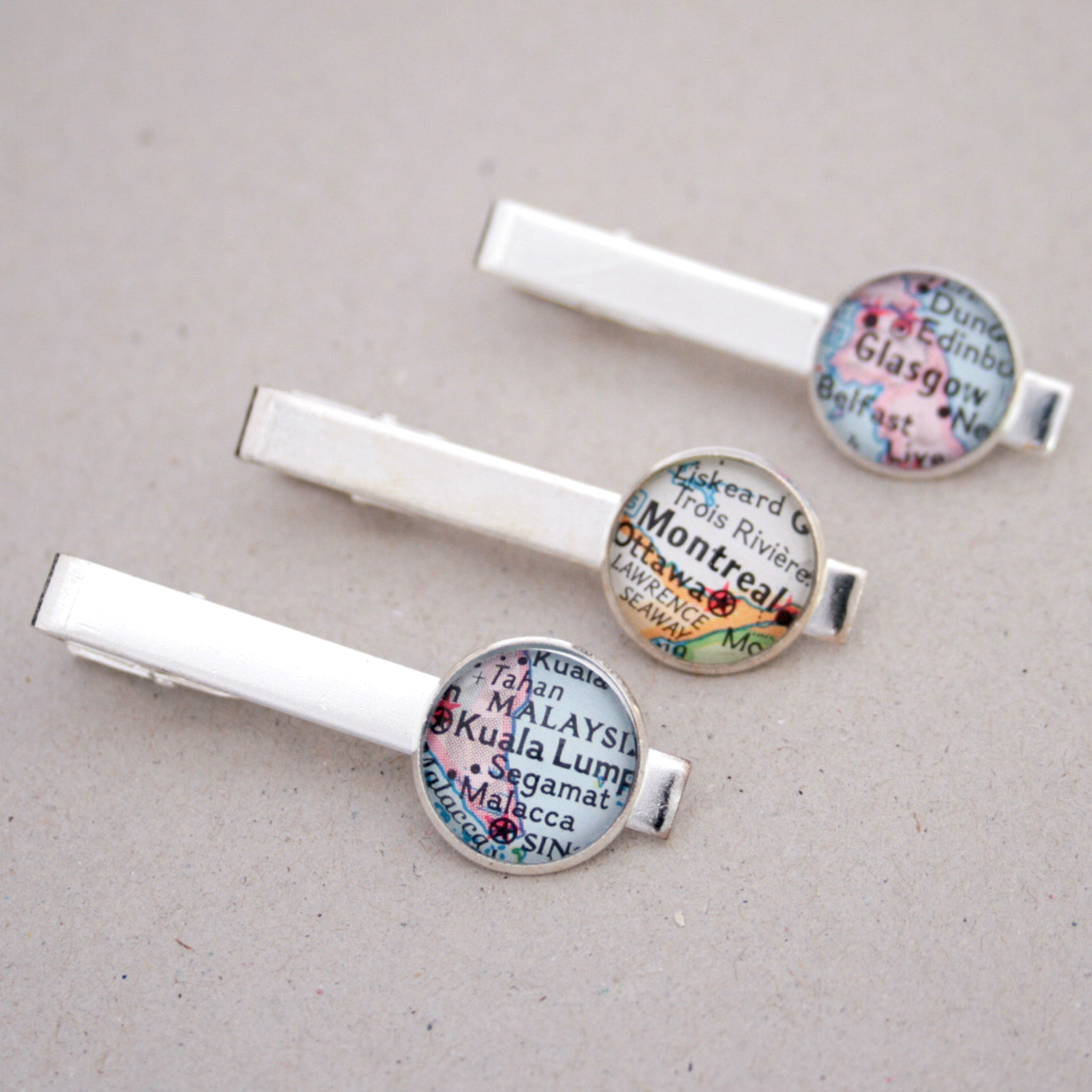 Three personalised tie clips in silver color featuring selection of maps