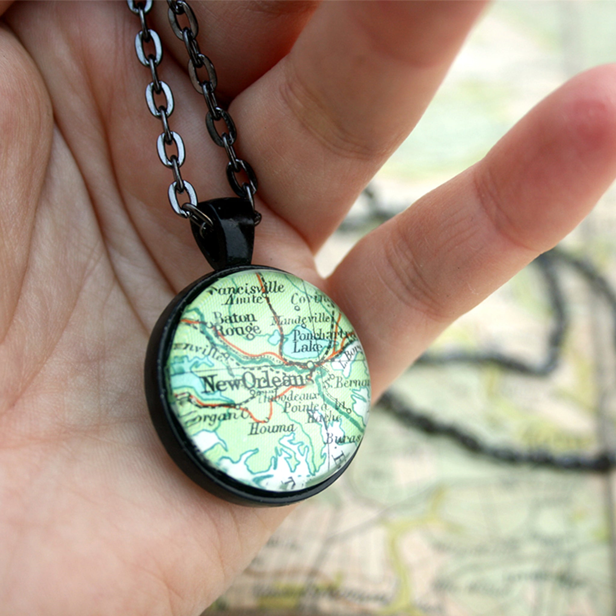 Hold in hand black double sided pendant necklace featuring map of New Orleans