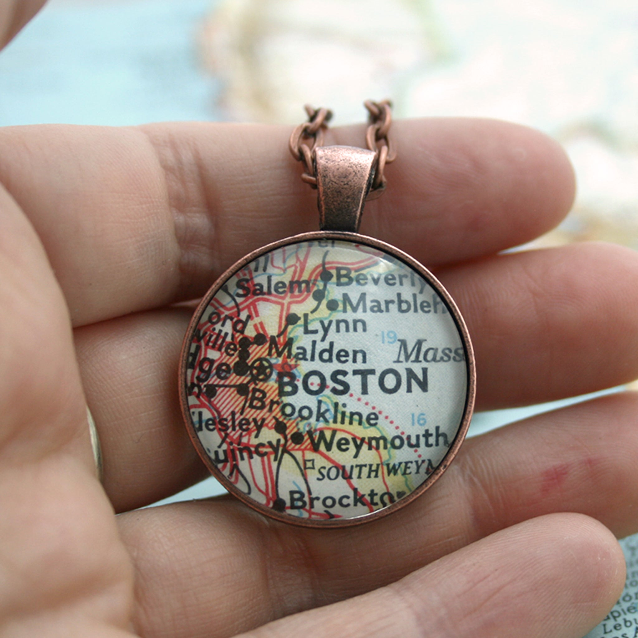 Copper double sided pendant necklace featuring map of Boston hold in hand