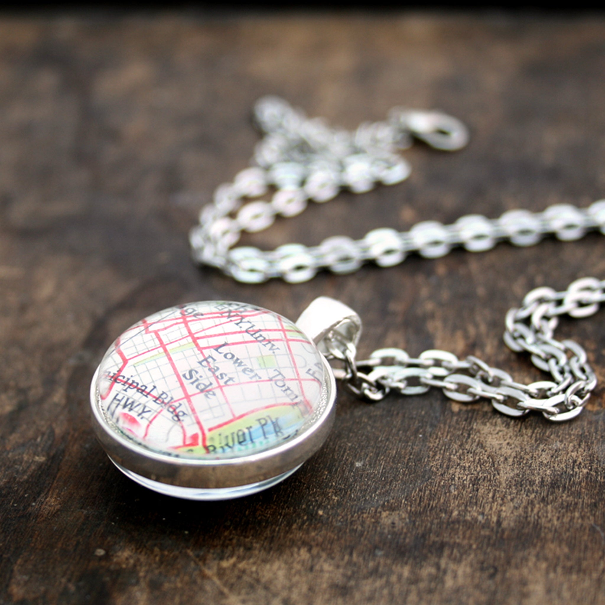 Silver tone double sided pendant necklace featuring map of New York City