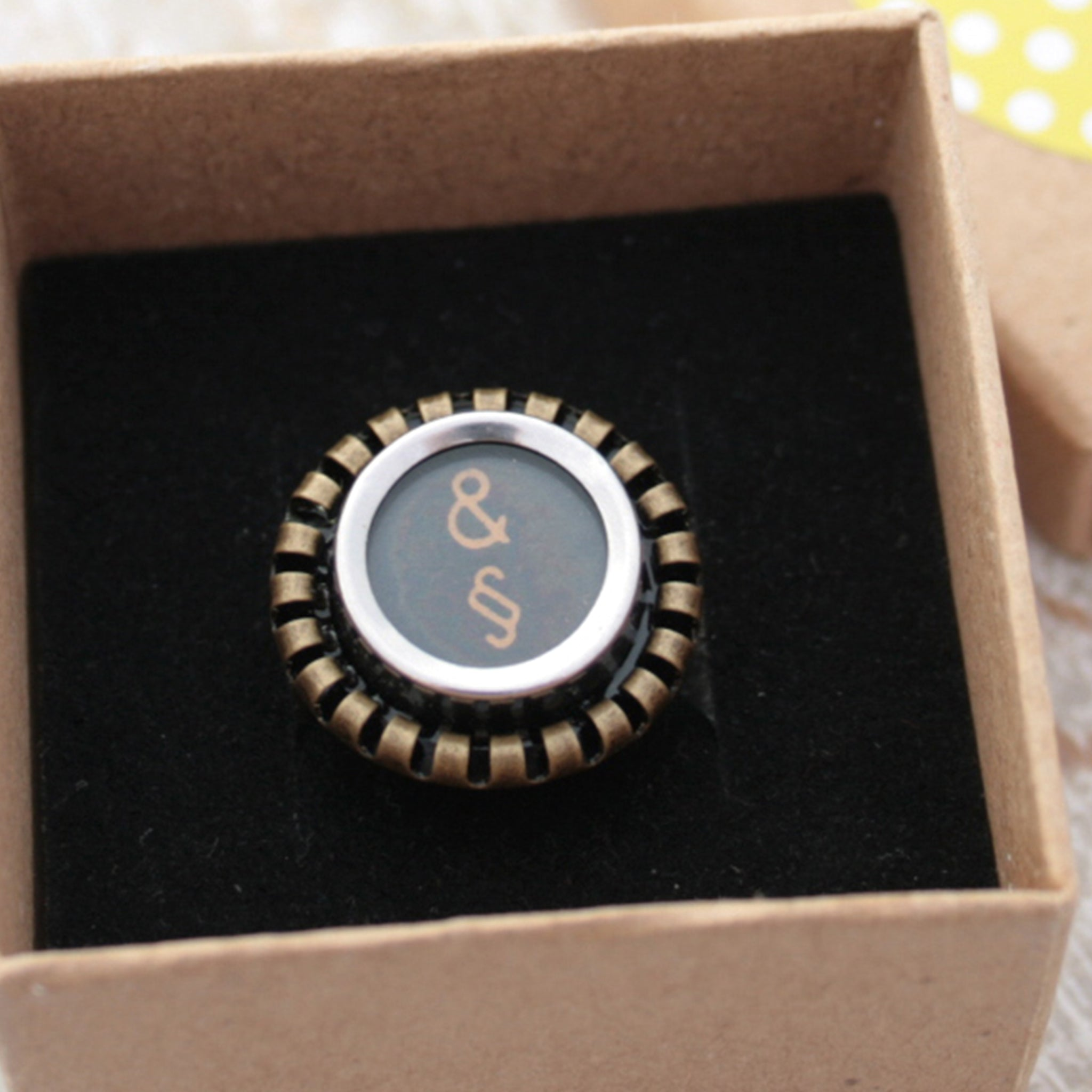 Black Ring featuring Amresand and paragraph signs made of typewriter key in a box