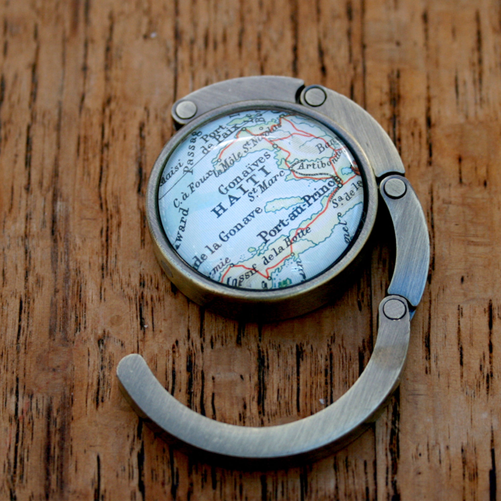 Purse hanger in bronze color featuring map of Haiti