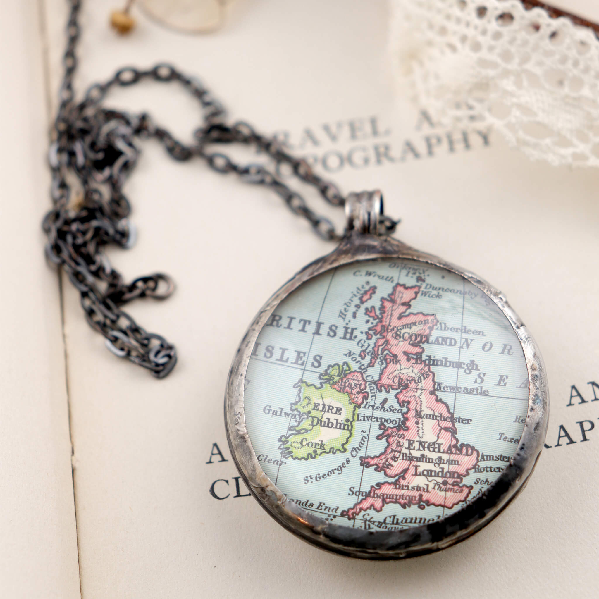 Map of British Isles framed into Tiffany style statement necklace lying on a book