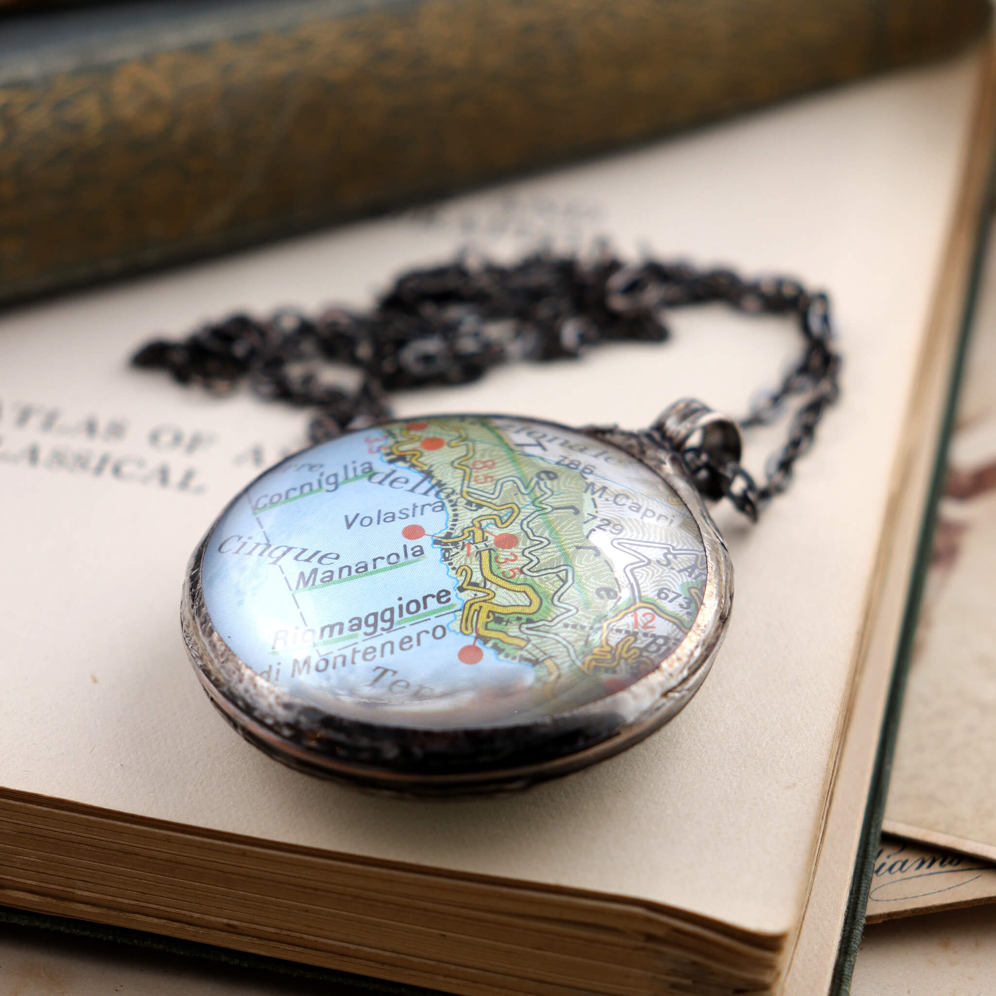 Riomaggiore map framed into Tiffany style statement necklace lying on a book