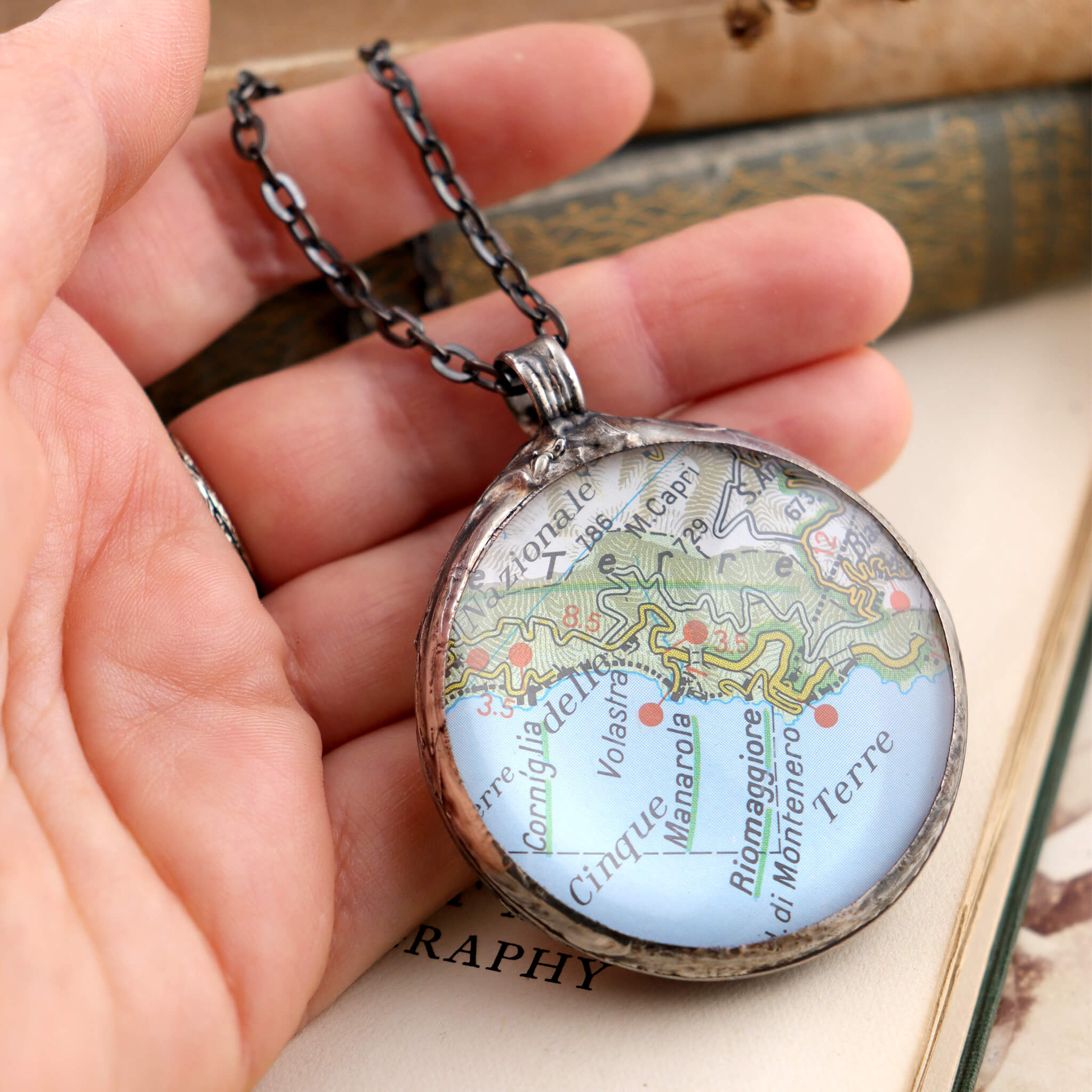 Riomaggiore map framed into Tiffany style statement necklace hold in hand