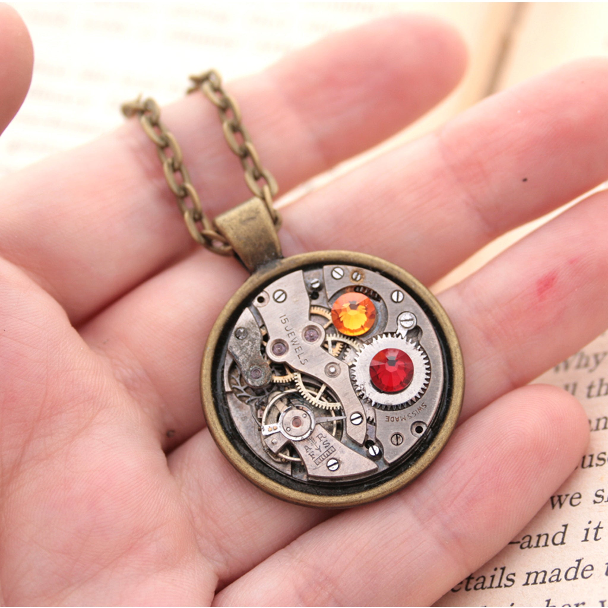 Dark academia necklace made of watch mechanism and Swarovski crystals lying on hand
