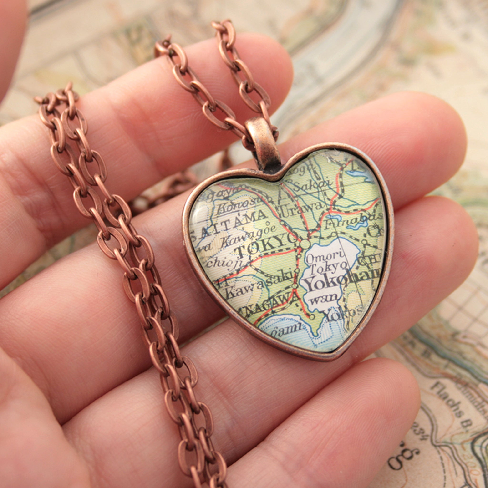 Hold in hand heart shaped pendant necklace in copper tone featuring map of Tokyo