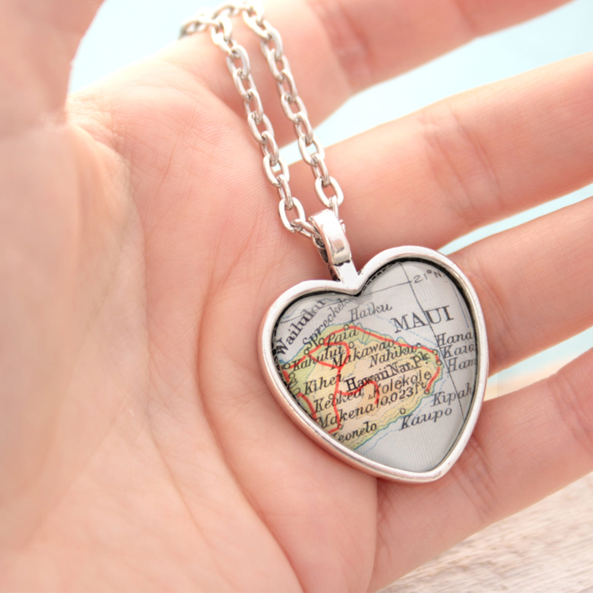 Hold in hand heart shaped pendant necklace in silver tone featuring map of Maui