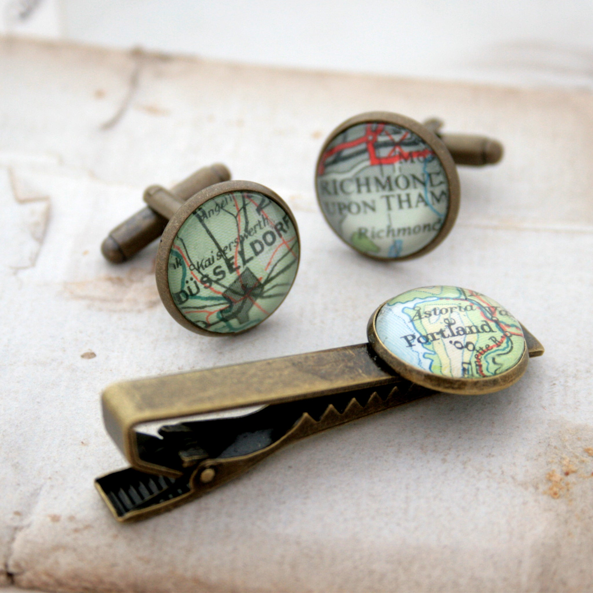 Tie clip and cufflinks in bronze color featuring selection of map locations