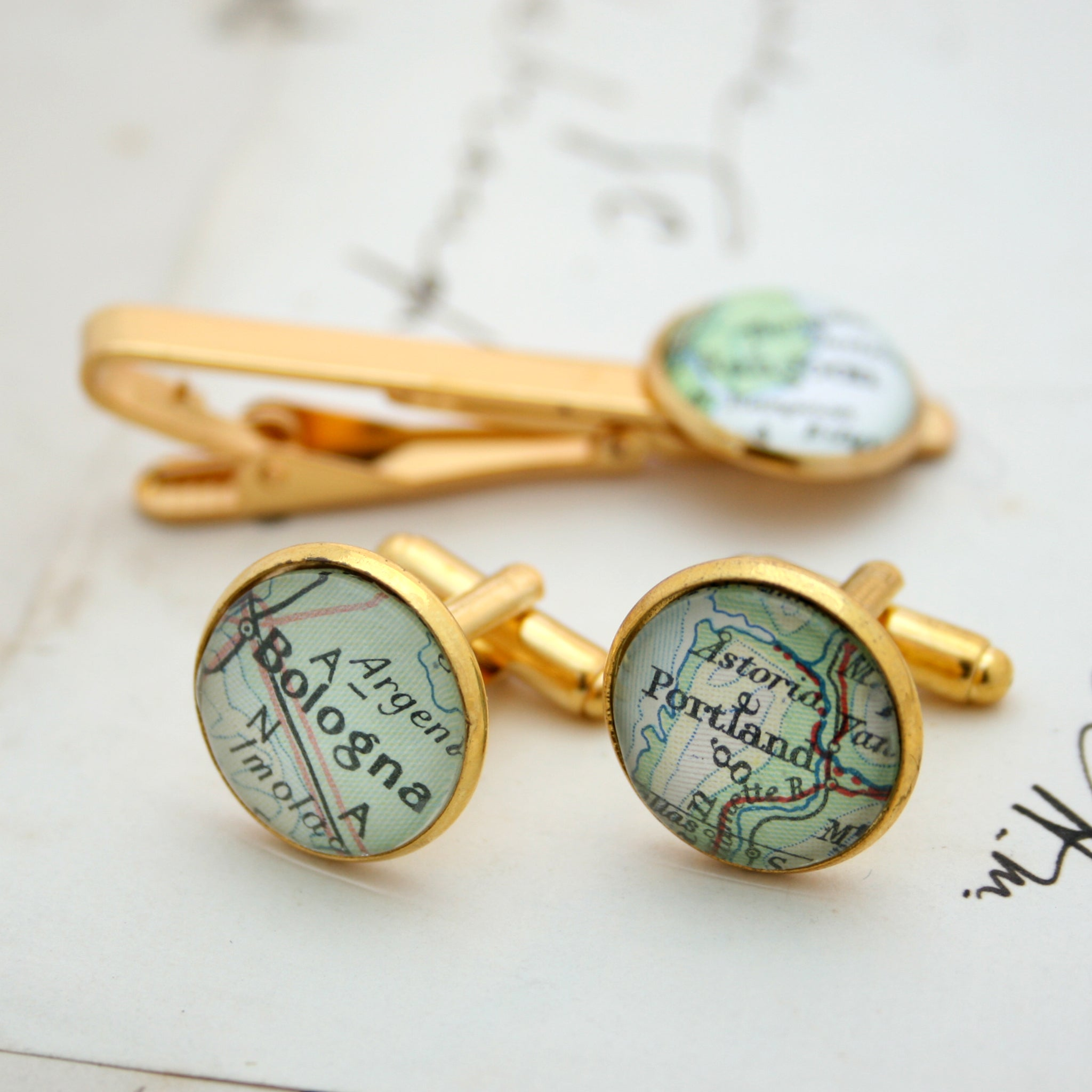 Tie clip and cufflinks in gold color featuring selection of map locations