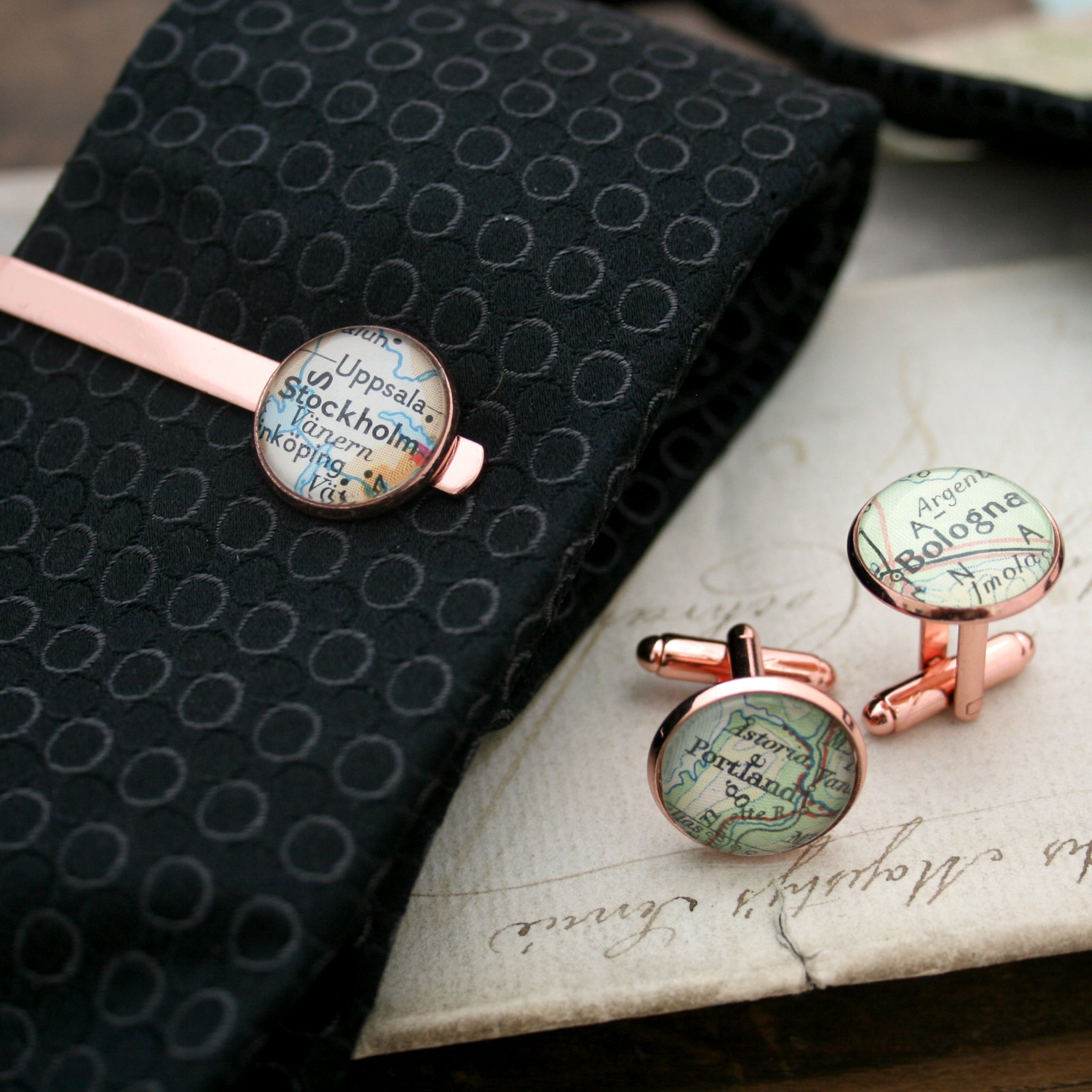 Tie clip on tie and cufflinks in rose gold color featuring selection of map locations