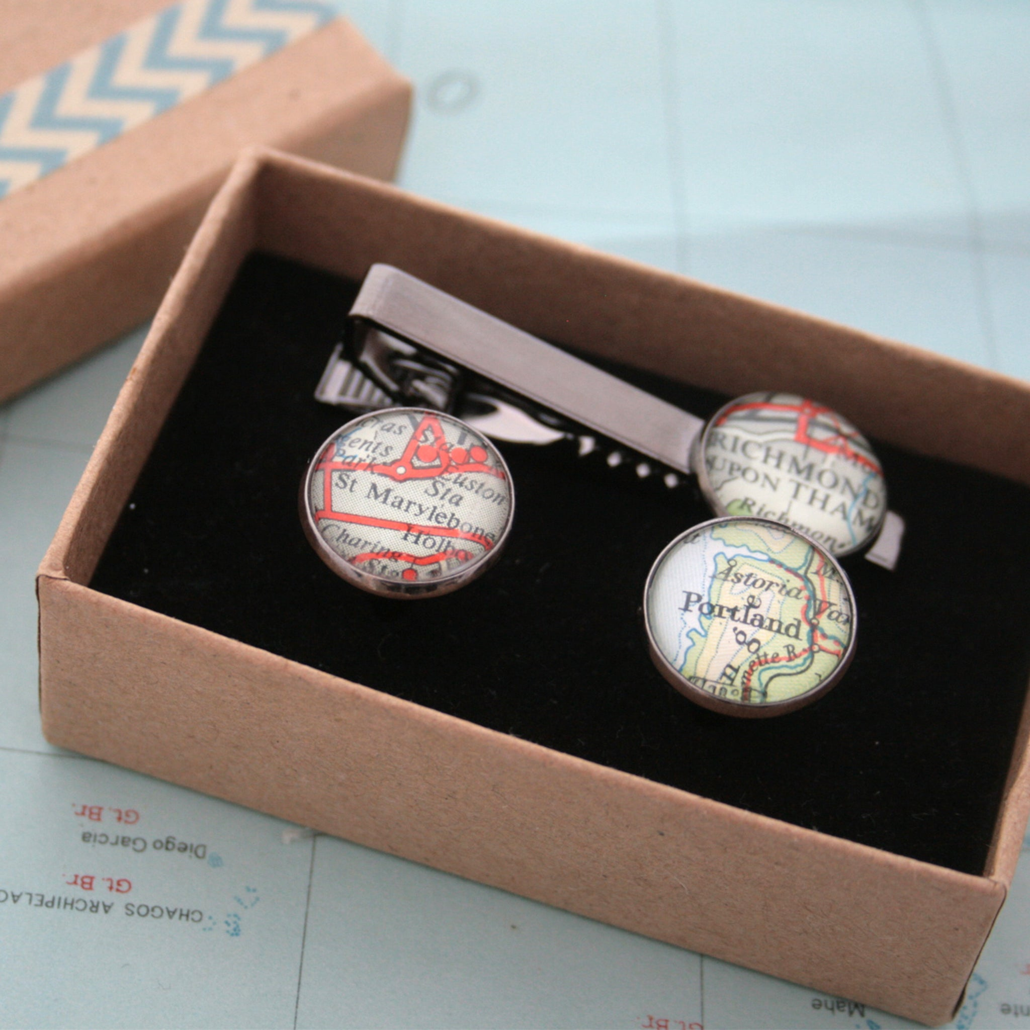 Tie clip and cufflinks in gunmetal black color featuring selection of map locations in a box