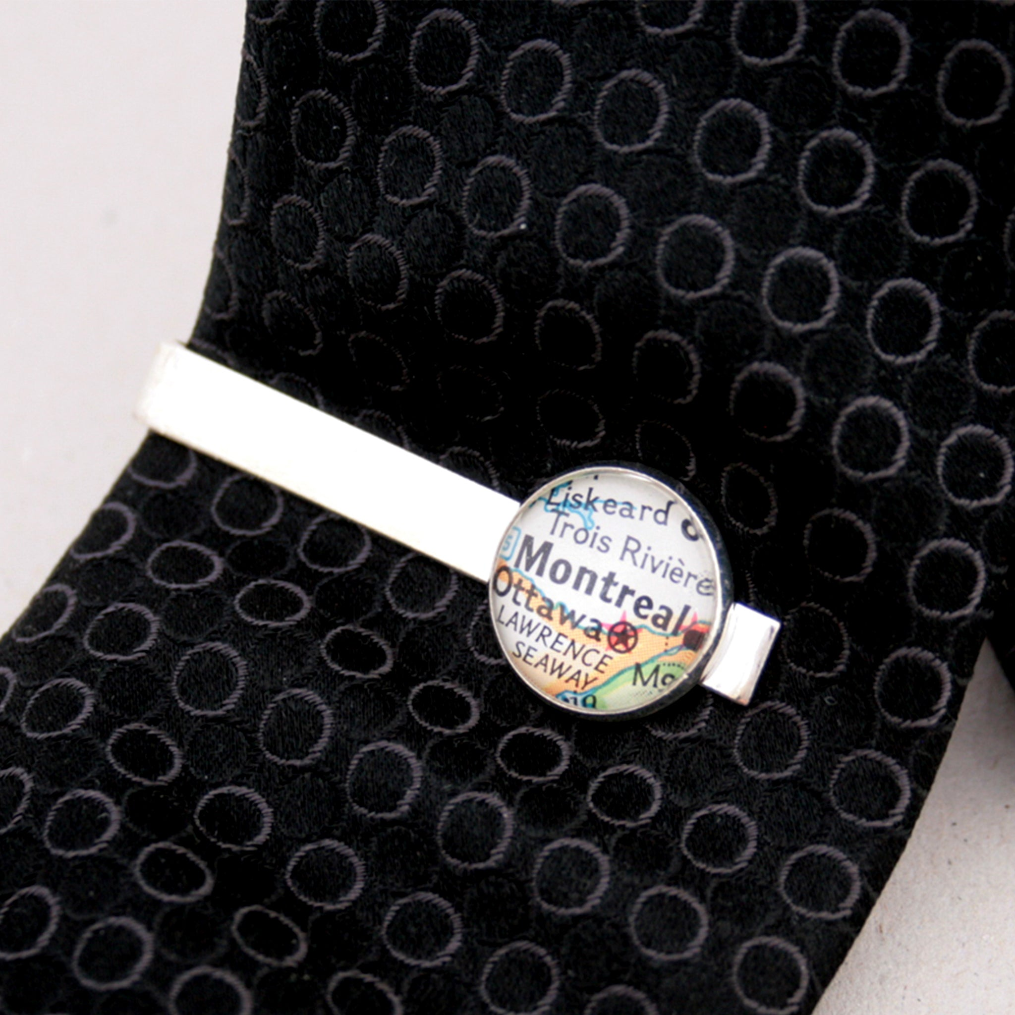 Tie clip in silver color featuring map of Montreal on a black tie