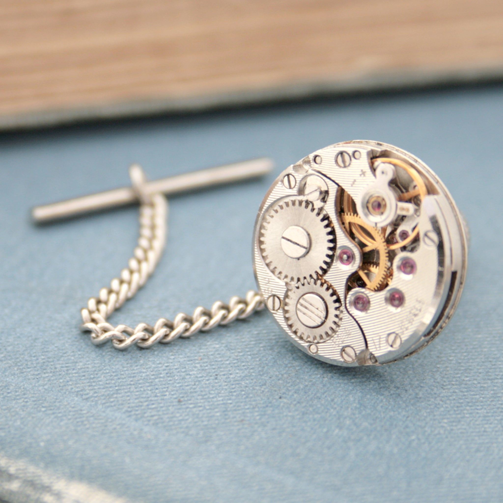 Tie tack with chain made of old watch movement