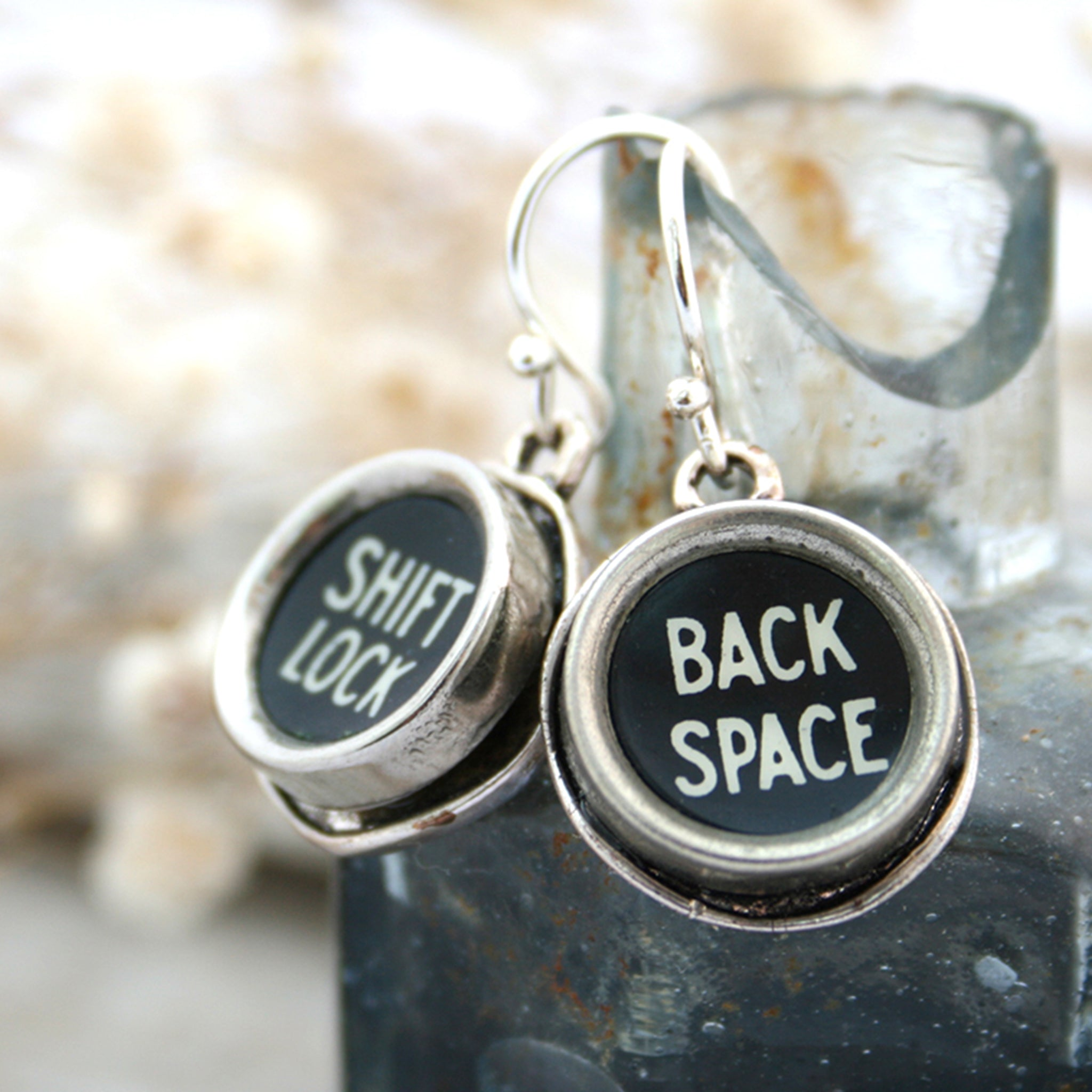 Typewriter keys Shift Lock and Back space earrings hanging from an inkwell