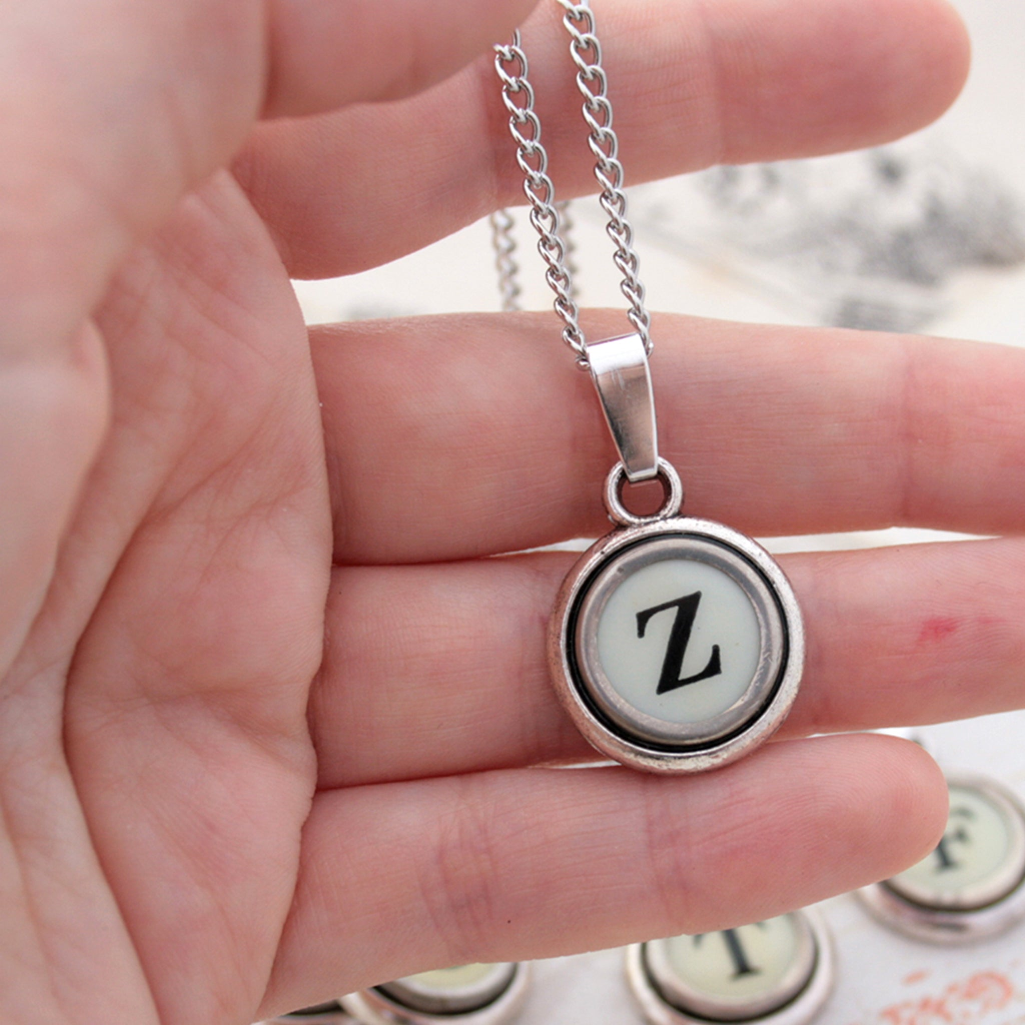 Ivory Z letter necklace made of typewriter key hold in hand