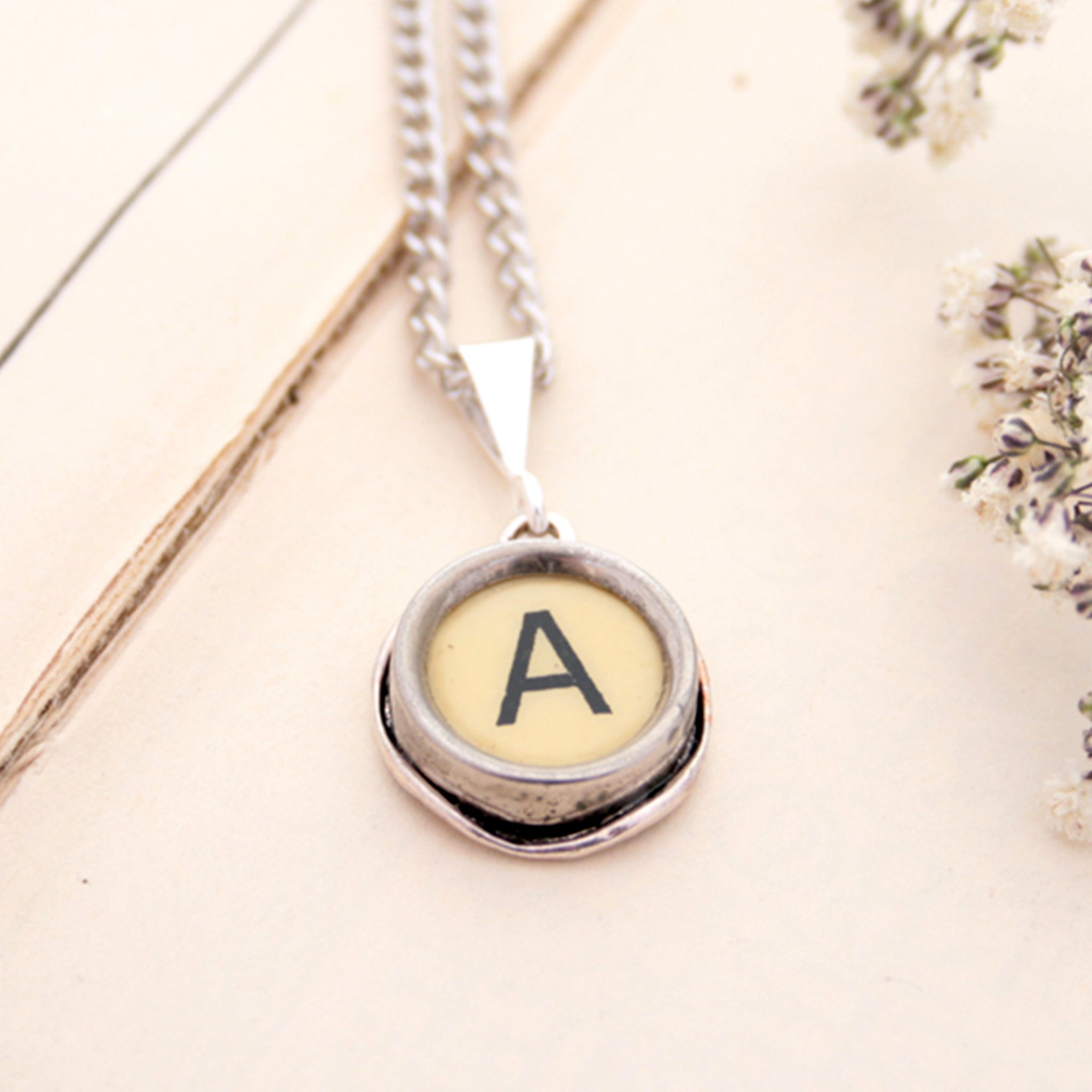 A letter necklace in ivory color made of vintage typewriter key