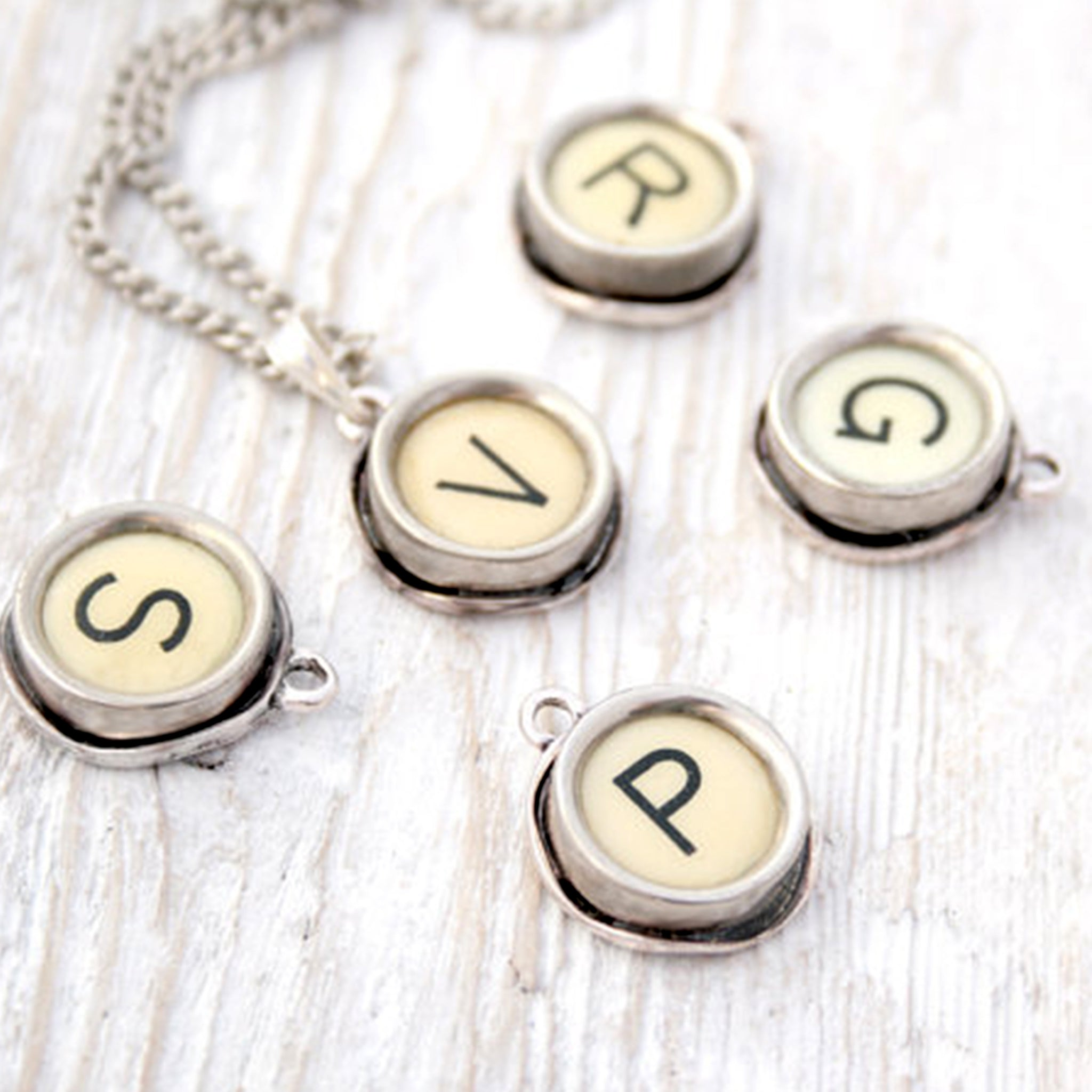Few ivory typewriter key necklaces lying on a white surface