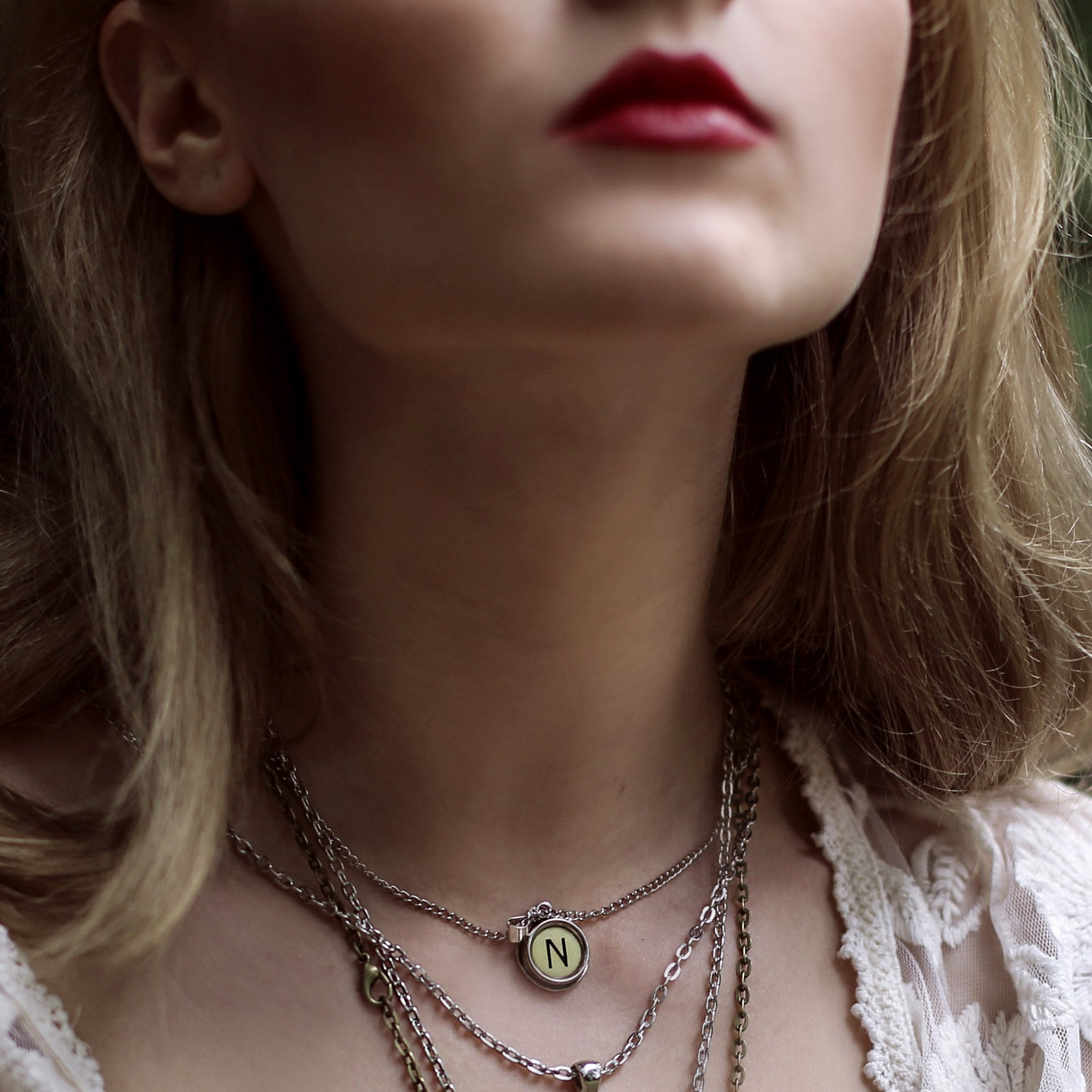 Model wearing initial necklace made of authentic vintage ivory typewriter key