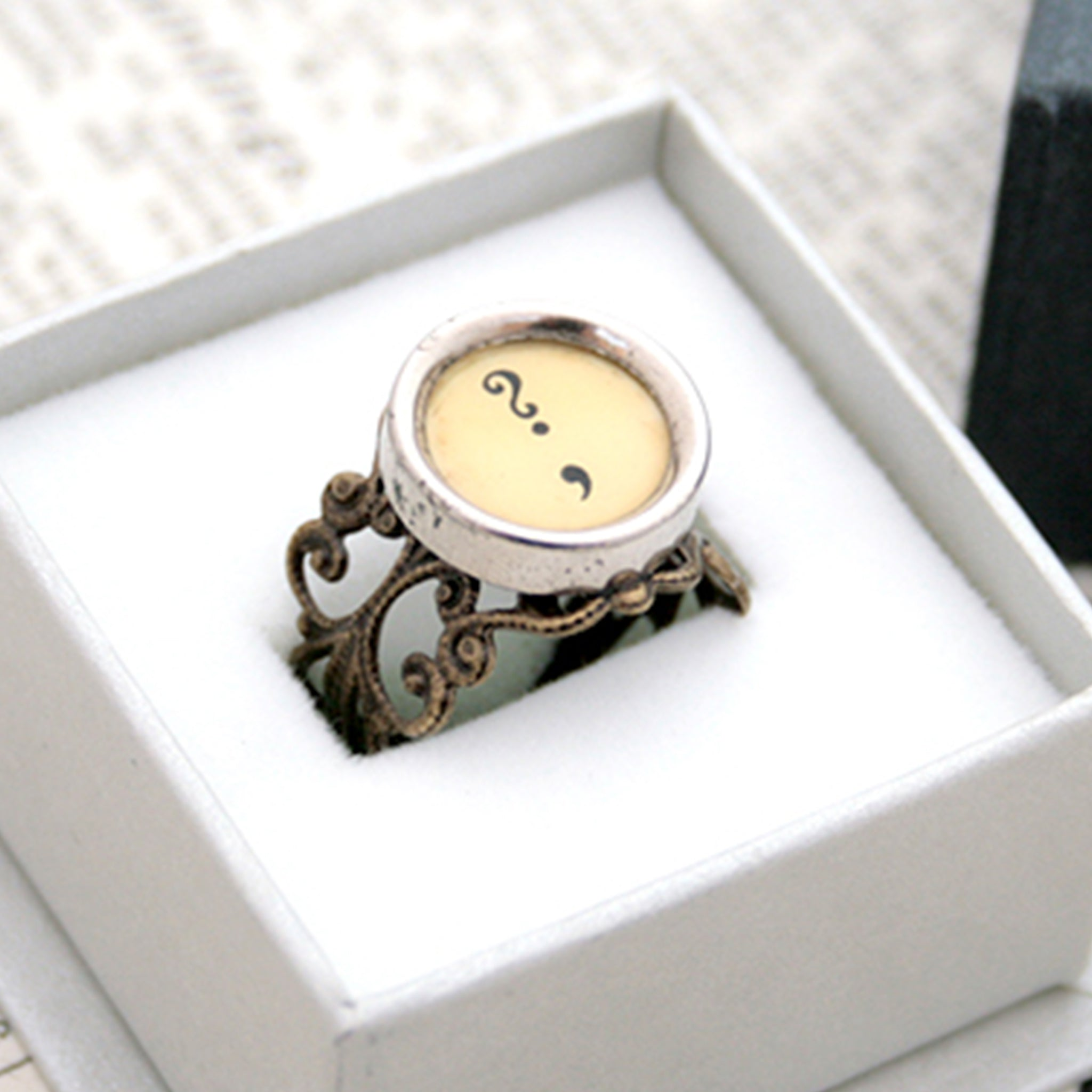 Ring with question mark and comma made of  typewriter key in ivory color in a box