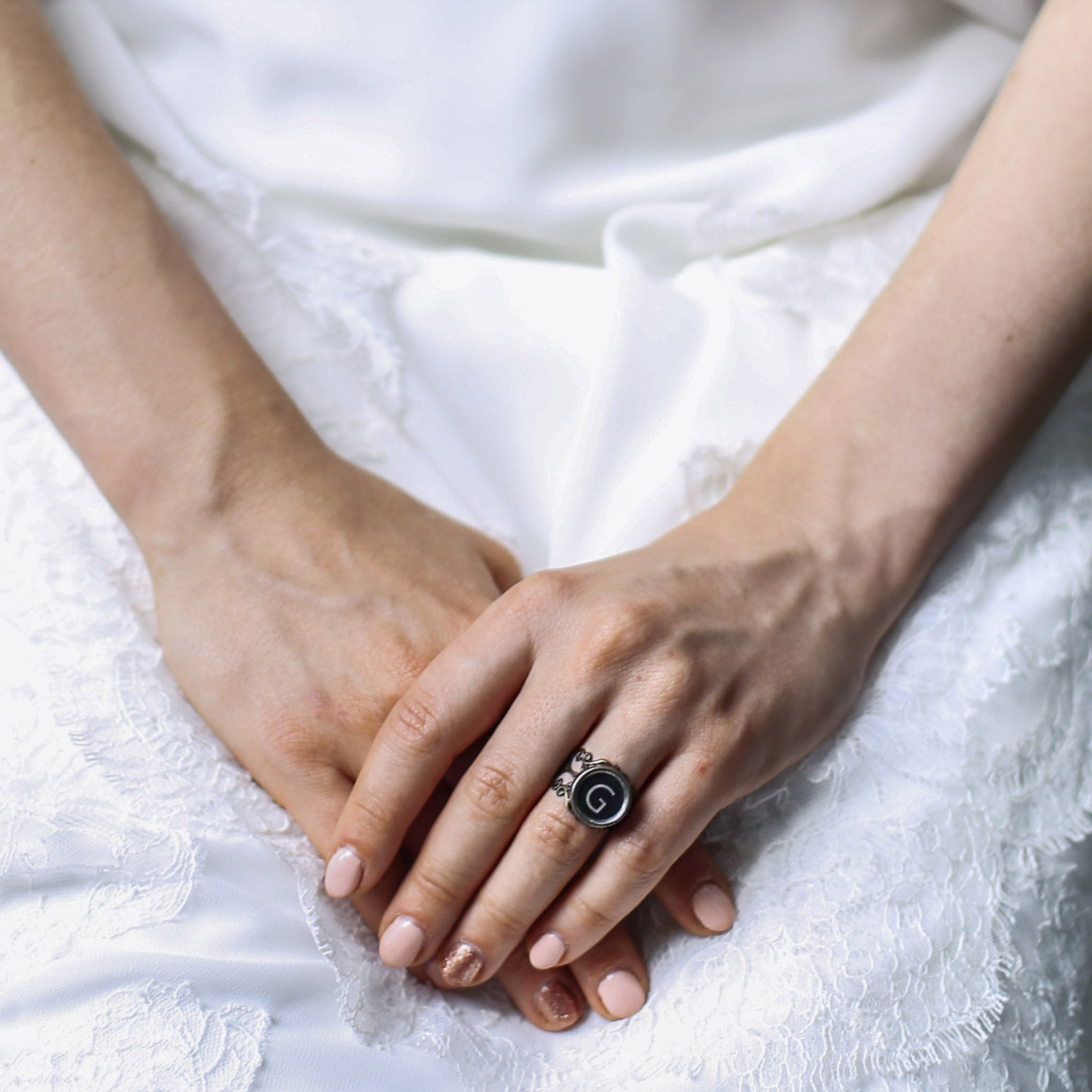 Bride wearing initial ring made of authentic vintage typewriter key in black color