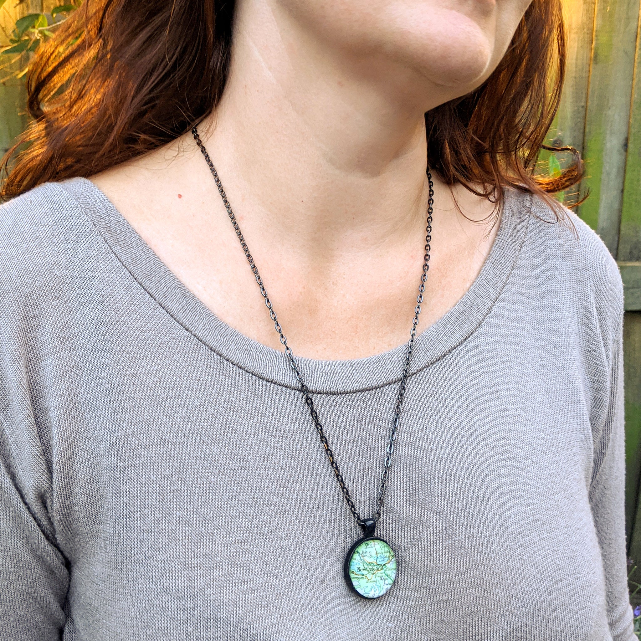 Two sided map necklace in black color worn by a woman