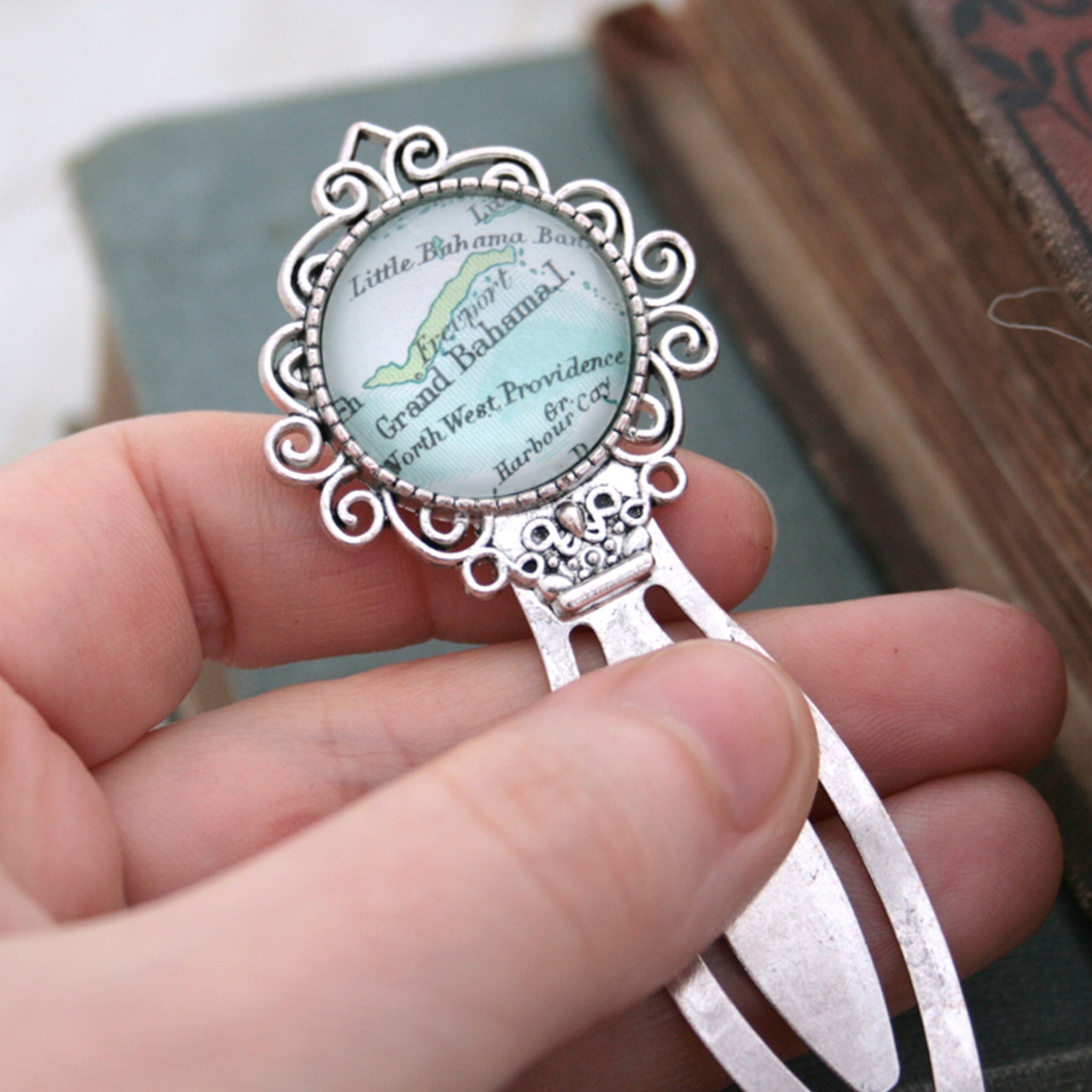Hand holding personalised bookmark featuring Grand Bahama map in silver color