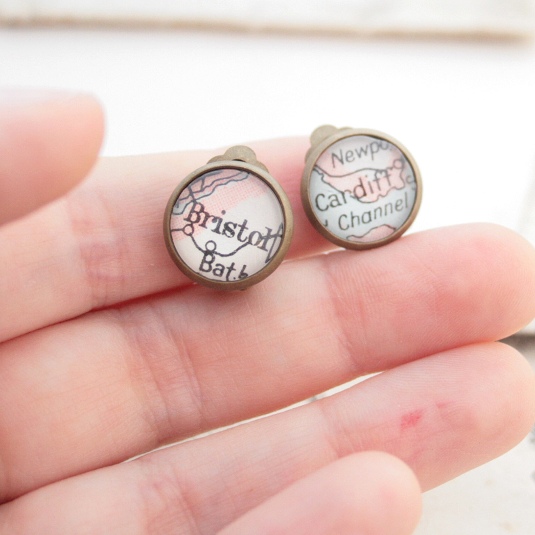Hold in hands Custom clip on earrings in bronze tone featuring vintage maps