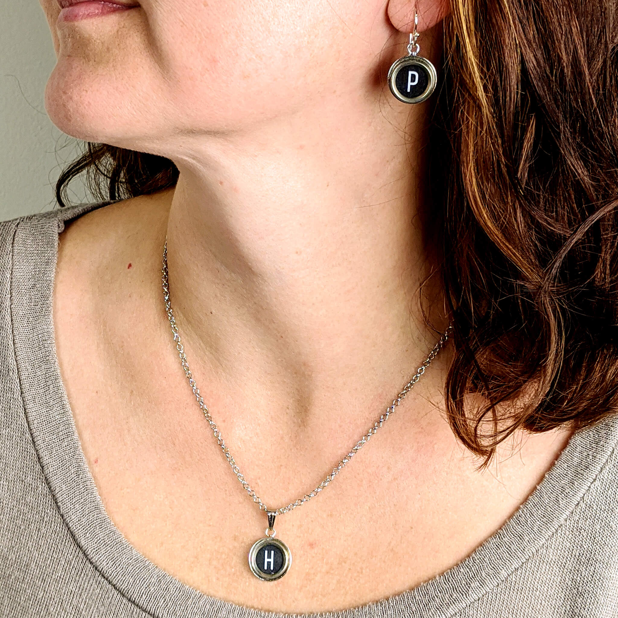 Woman wearing typewriter key necklace and earrings