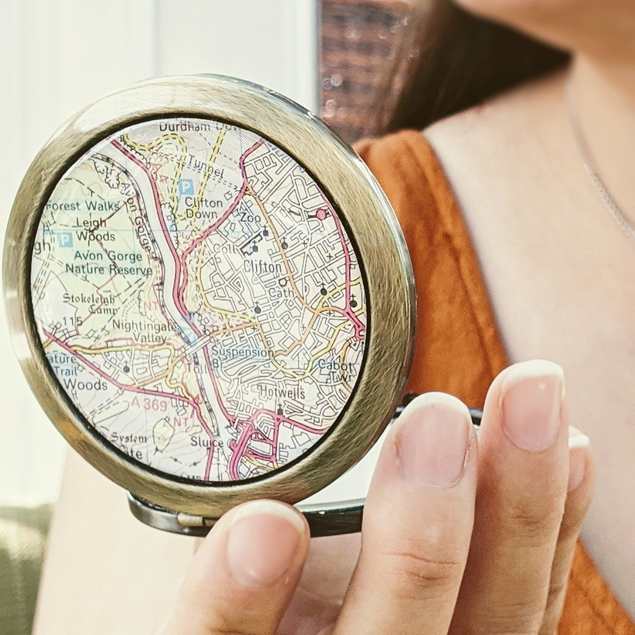 woman checking her makeup in custom map compact mirror