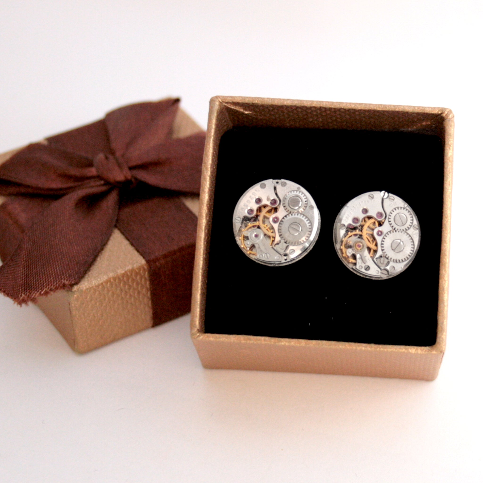 Round watch cufflinks in steampunk style featuring antique watch movements in a brown box